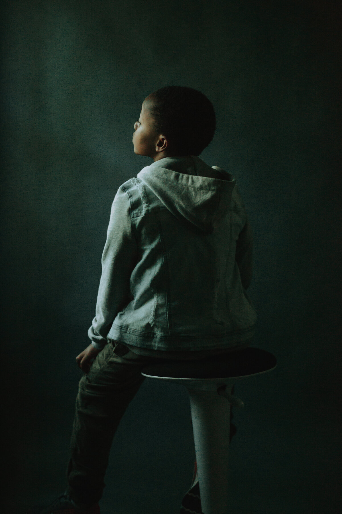 Picture of a boy sitting on a stool, facing away from the camera. Houston Fine Art Portraits.