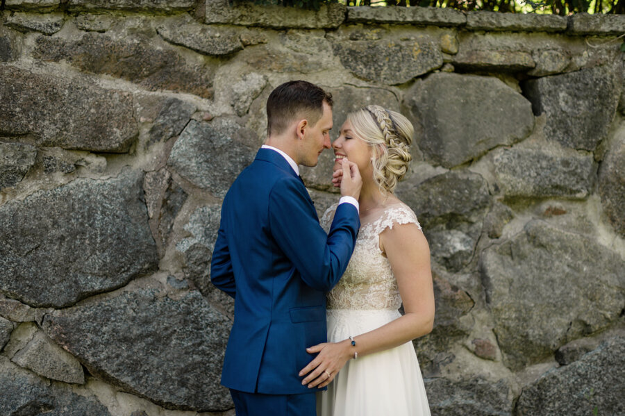 Bride and groom standing in front of stone wall and holding each other lovingly and smiling