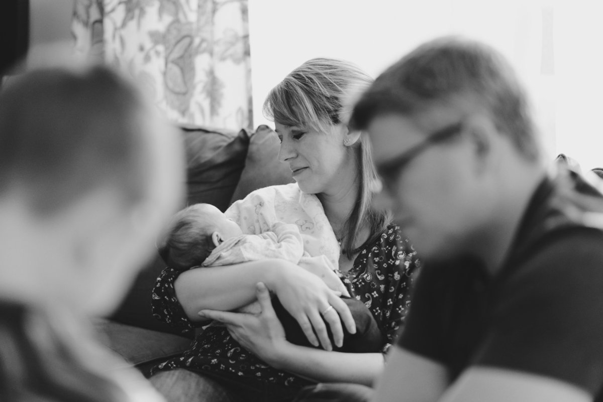 Mom holding newborn baby girl while her son and husband play legos