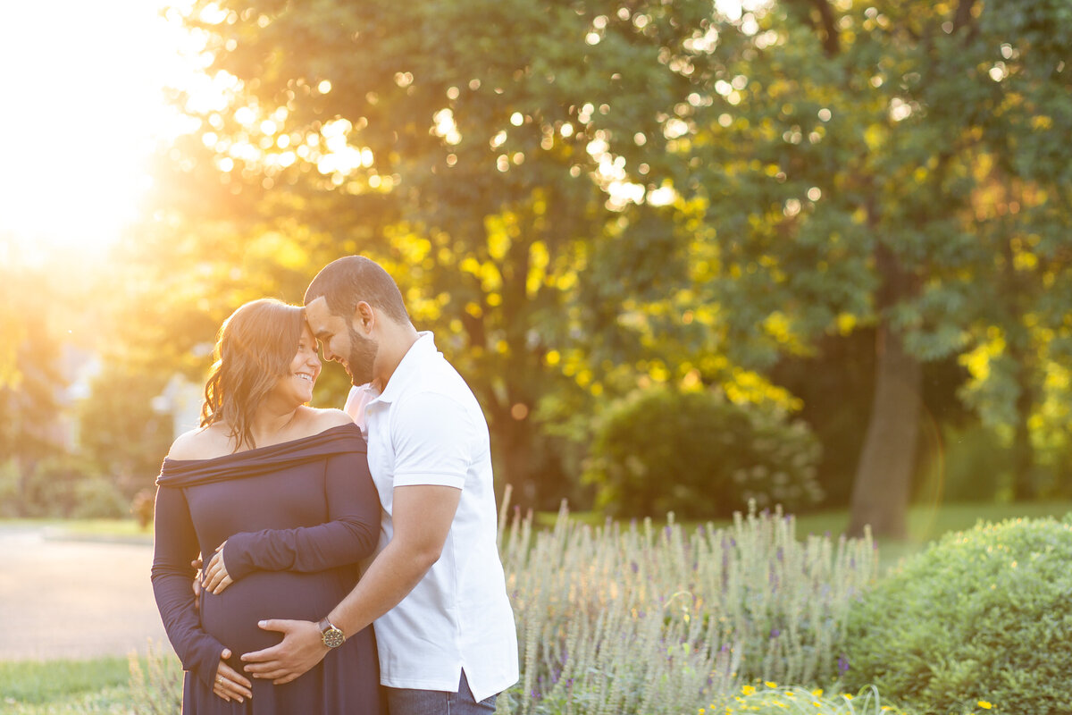 Spring Sunset Maternity Session with blue maxi dress standing by lavender  at Oak Knoll Park in St. Louis by Amy Britton Photography Photographer  in St. Louis