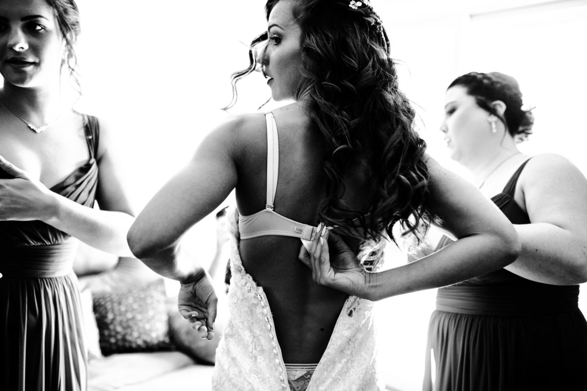 One of the top wedding photos of 2019. Taken by Adore Wedding Photography- Toledo Ohio Wedding Photographers. This photo is of bride unhooking her bra while she gets into her dress before the wedding
