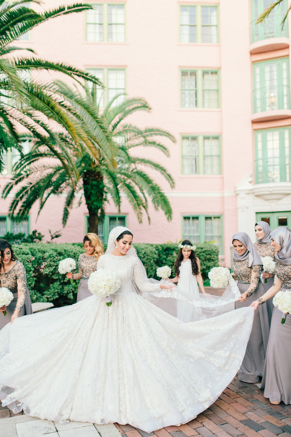 Bride & bridesmaids walking together holding brides dress