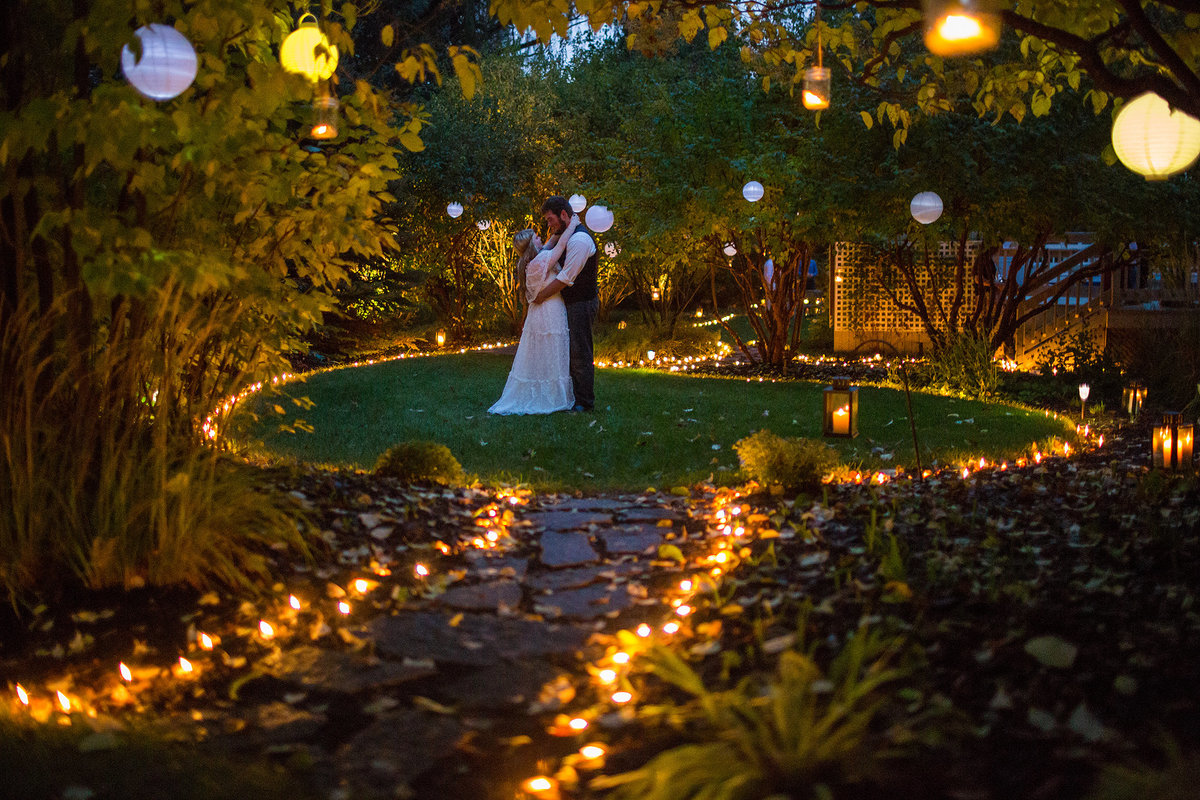 young couple getting married in backyard with lights