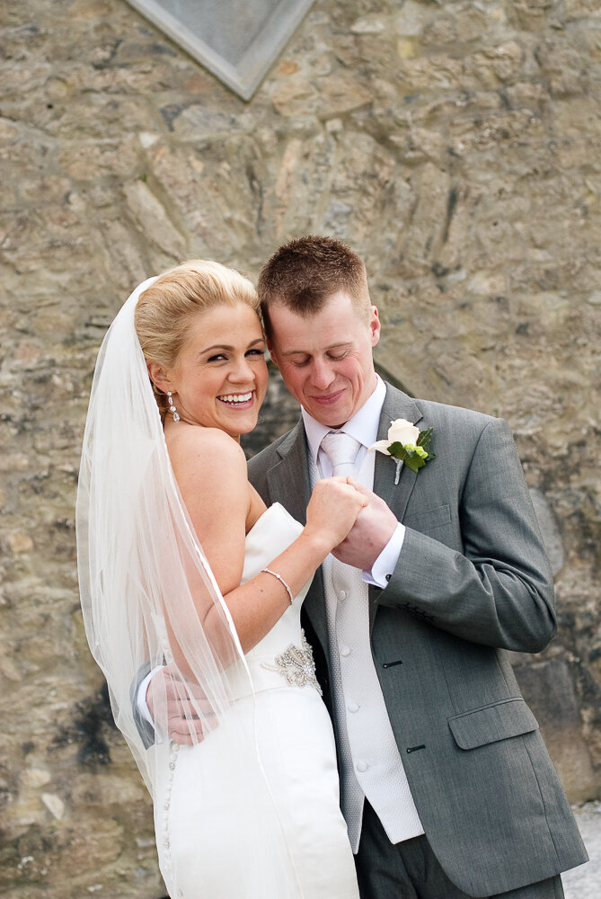 blonde bride wearing a mermaid dress and long veil embracing her husband who is wearing a light grey suit and white tie in front of Ross Castle in Killarney