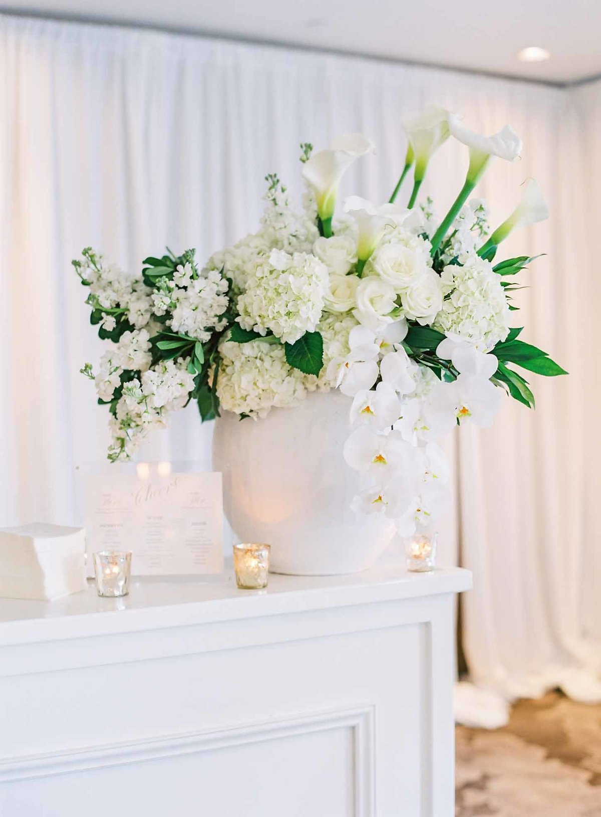 Large statement piece bar flowers filled with white callas, hydrangea and orchids create a WOW!