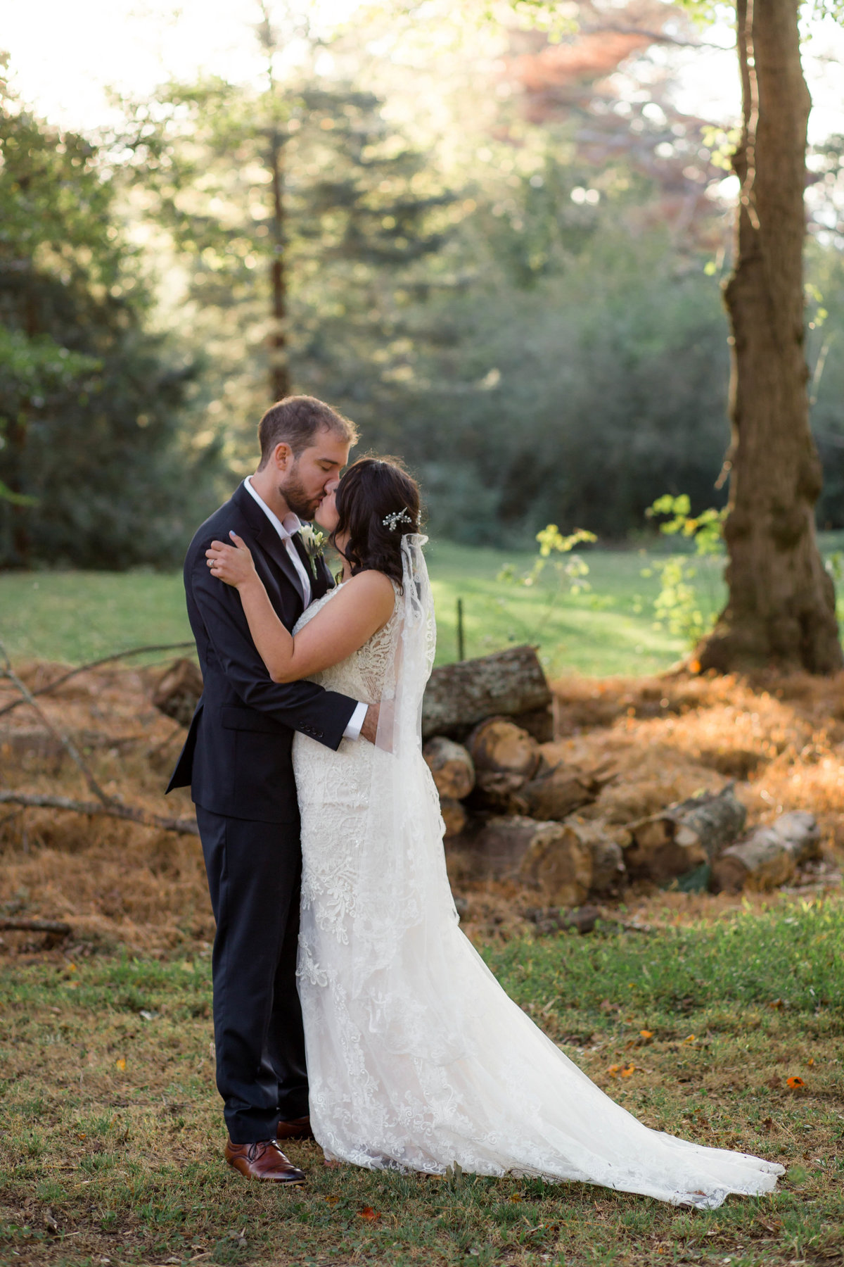 bride and grrom kiss in beautiful backyard wedding for wedding photographer