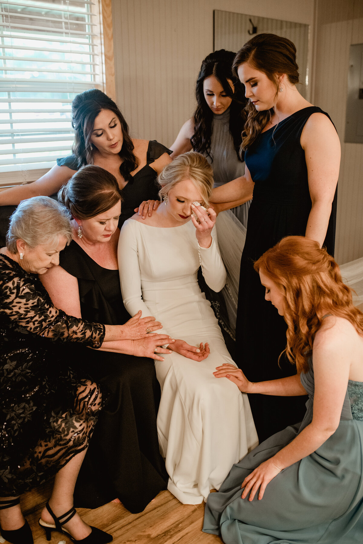 Bride prays with bridesmaids before ceremony, captured by documentary style wedding photographer