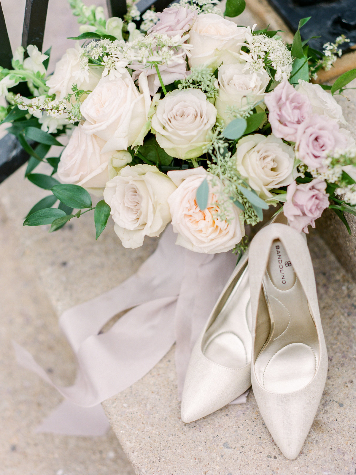 bouquet sitting next to neutral wedding shoes