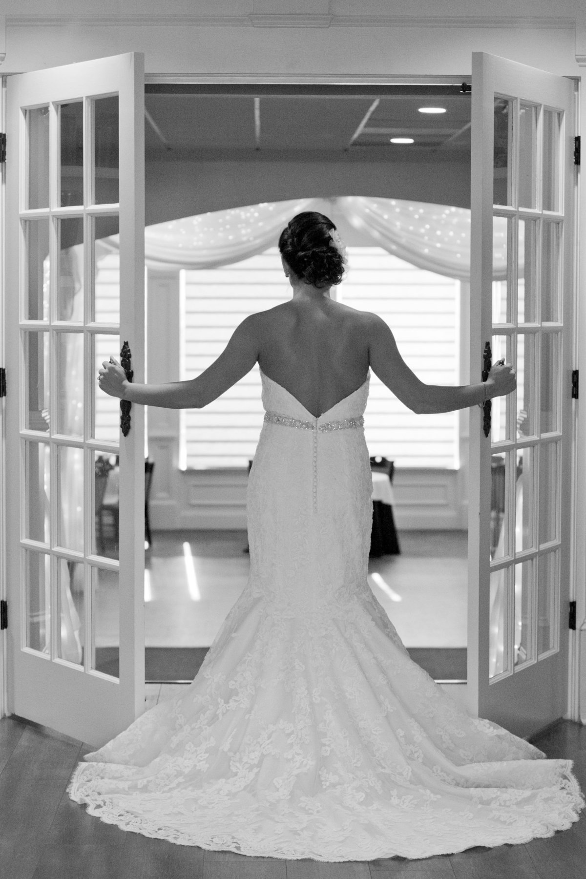 black and white of bride opening doors to reception