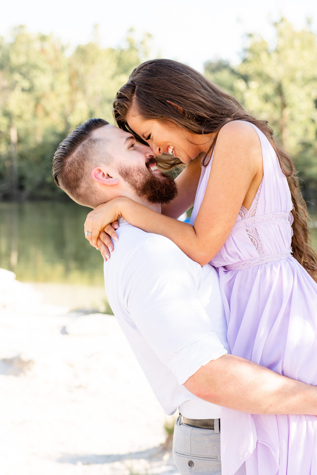 Summer Sunset Romantic Engagement Session in lavender maxi dress guy lifting girl by water at Klondike Park in St. Louis by Amy Britton Photography Photographer in St. Louis