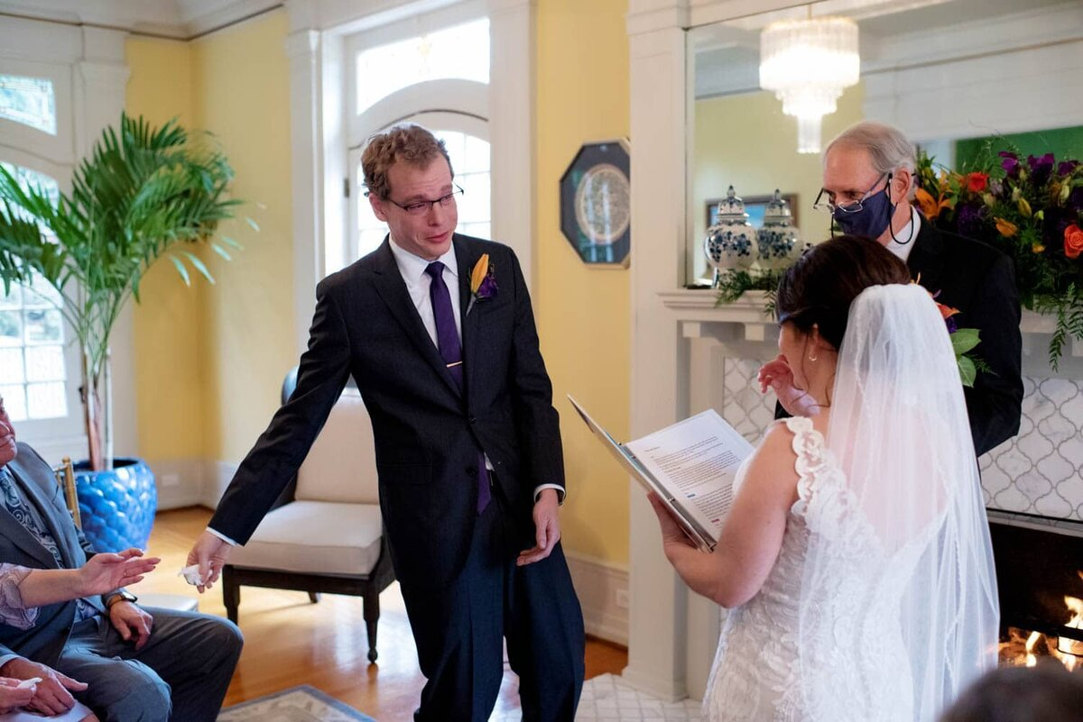 a groom reaches for a tissue to hand to the bride as she reads her wedding vows