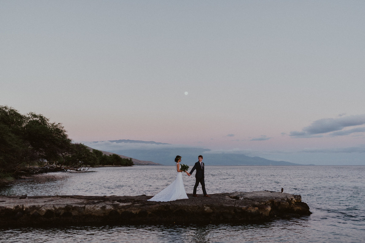 Bride and groom walk out on pier at sunset on Maui Hawaii at Olowalu Plantation House