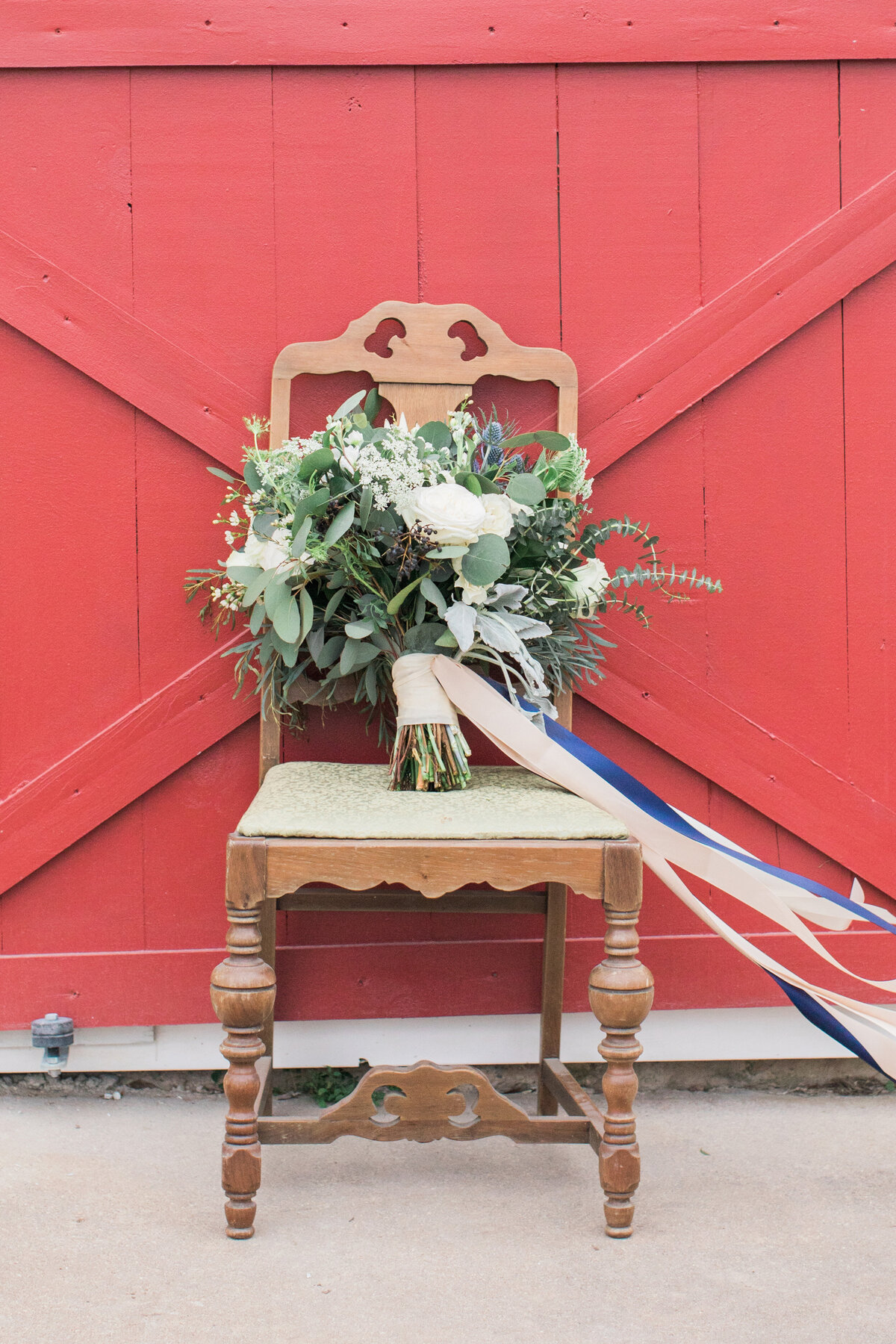 A rustic vintage chair holding a bridal bouquet in front of a red barn door