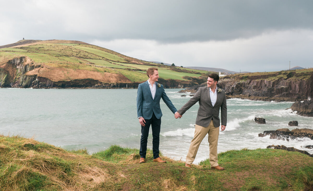 Two grooms standing on cliff overlooking sea in Kerry