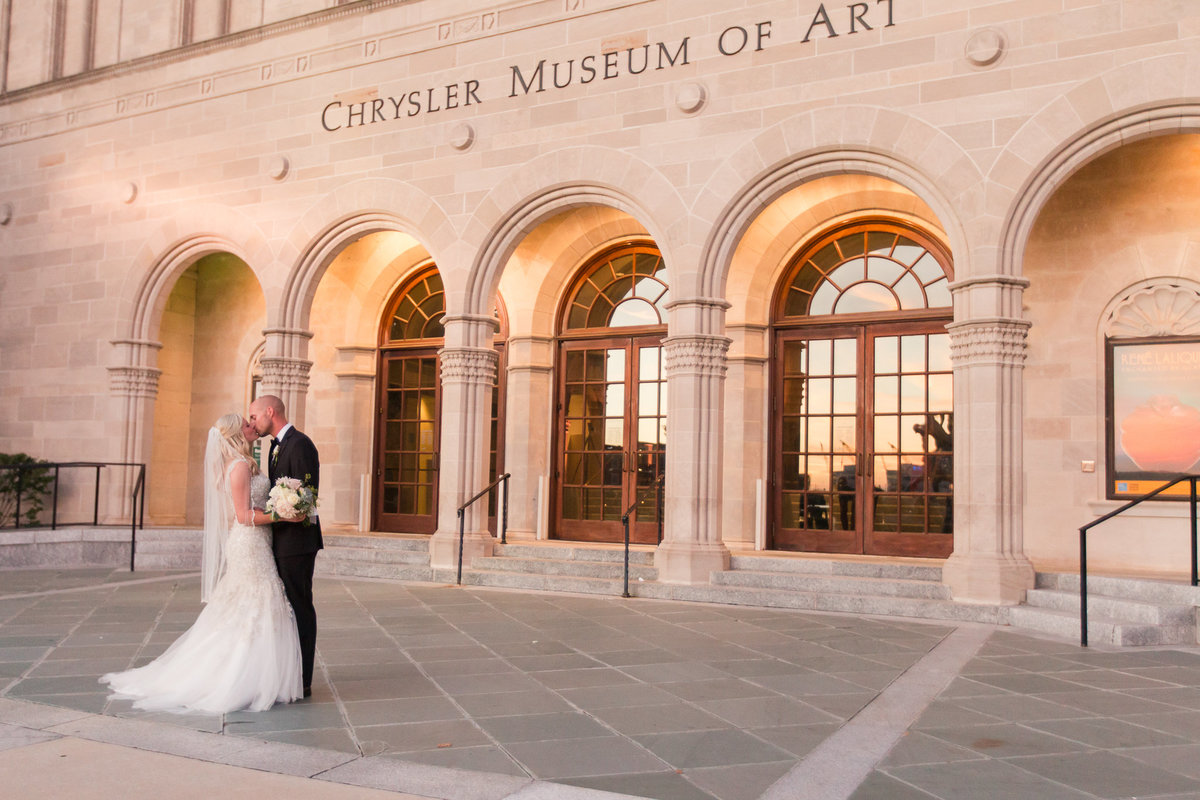 Bride and groom kissing at sunset in front of Chrysler Museum of Art