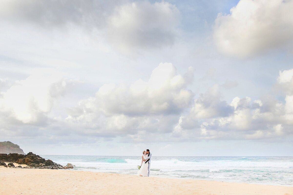 Wide portrait of bride and groom standing on the sand after their Kauai wedding
