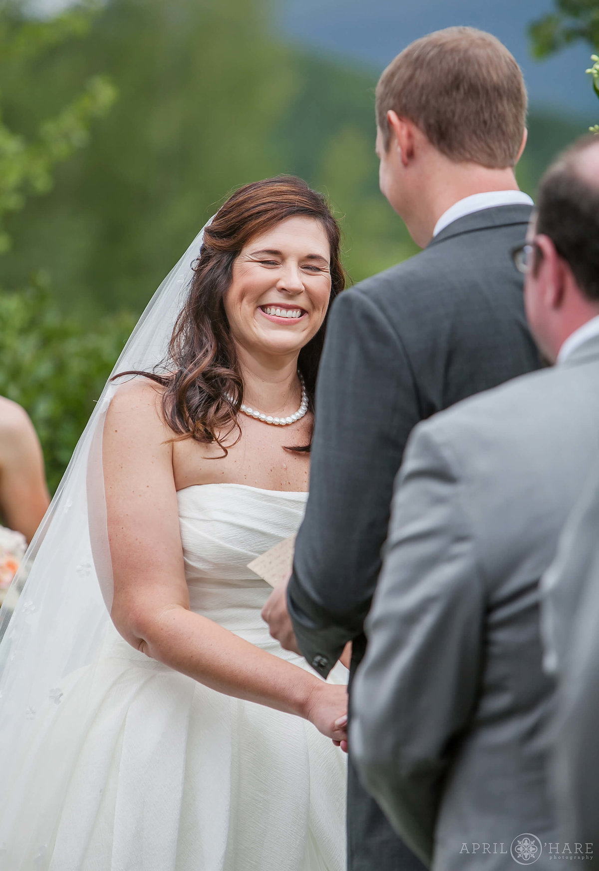 Sweet wedding photo of bride laughing at her outdoor Colorado wedding at Mountain wedding garden Crested Butte