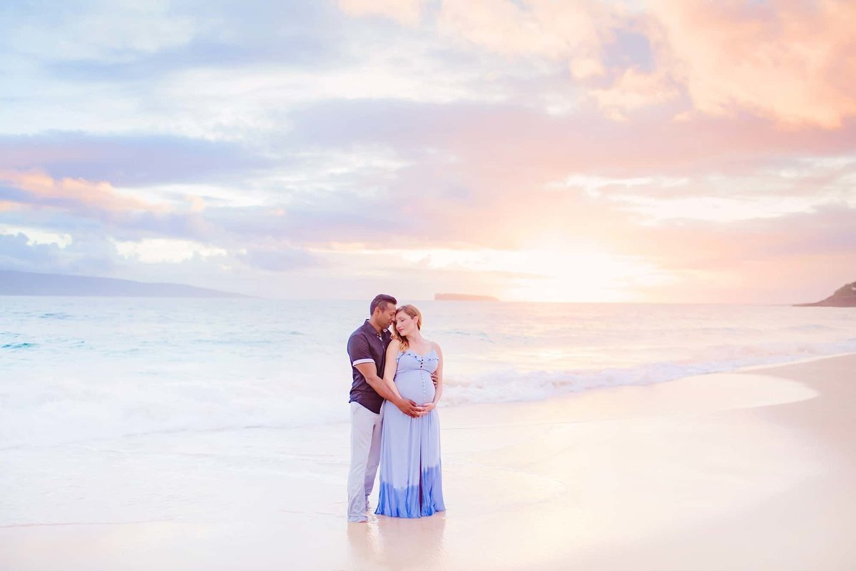 Husband kisses wife on the forehead in Makena during Maui maternity portrait session