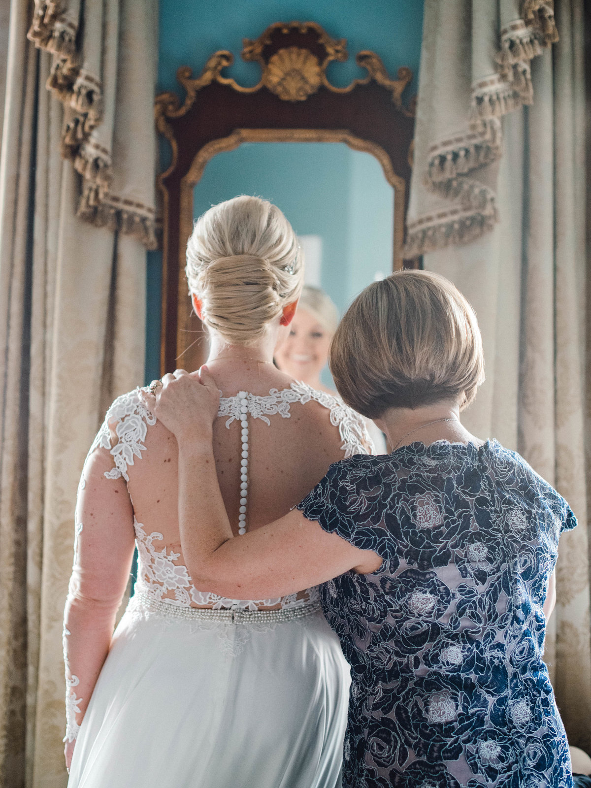 Bride and Mother looking in mirror before ceremony