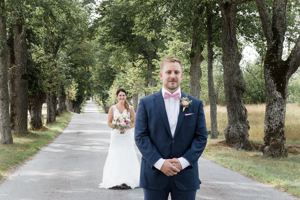 Groom waiting for his bride on first look in an alley close by Östra Ryd church