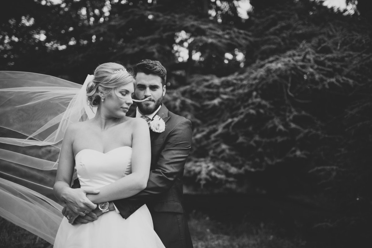 b&w photo of bride with veil flowing in wind and groom