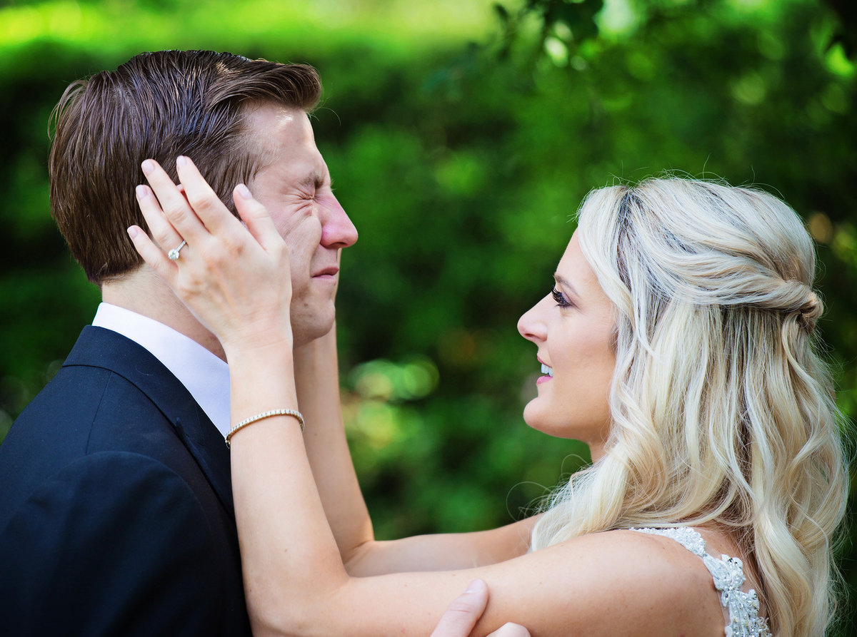 groom cries as he sees his bride for the first time in the Botanical Gardens of City Park in New Orleans