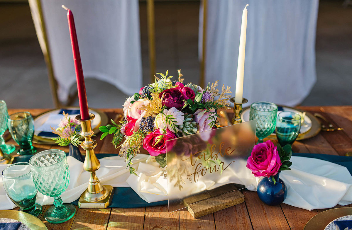 Rich jewel toned wedding flowers with gold and sea glass table decor