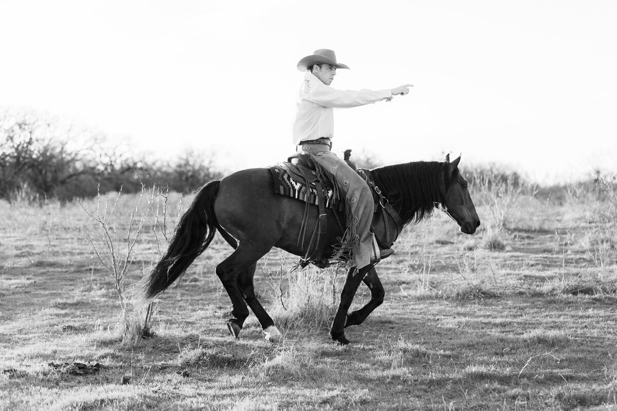 cowboy riding his horse bridle less with his arms stretched out