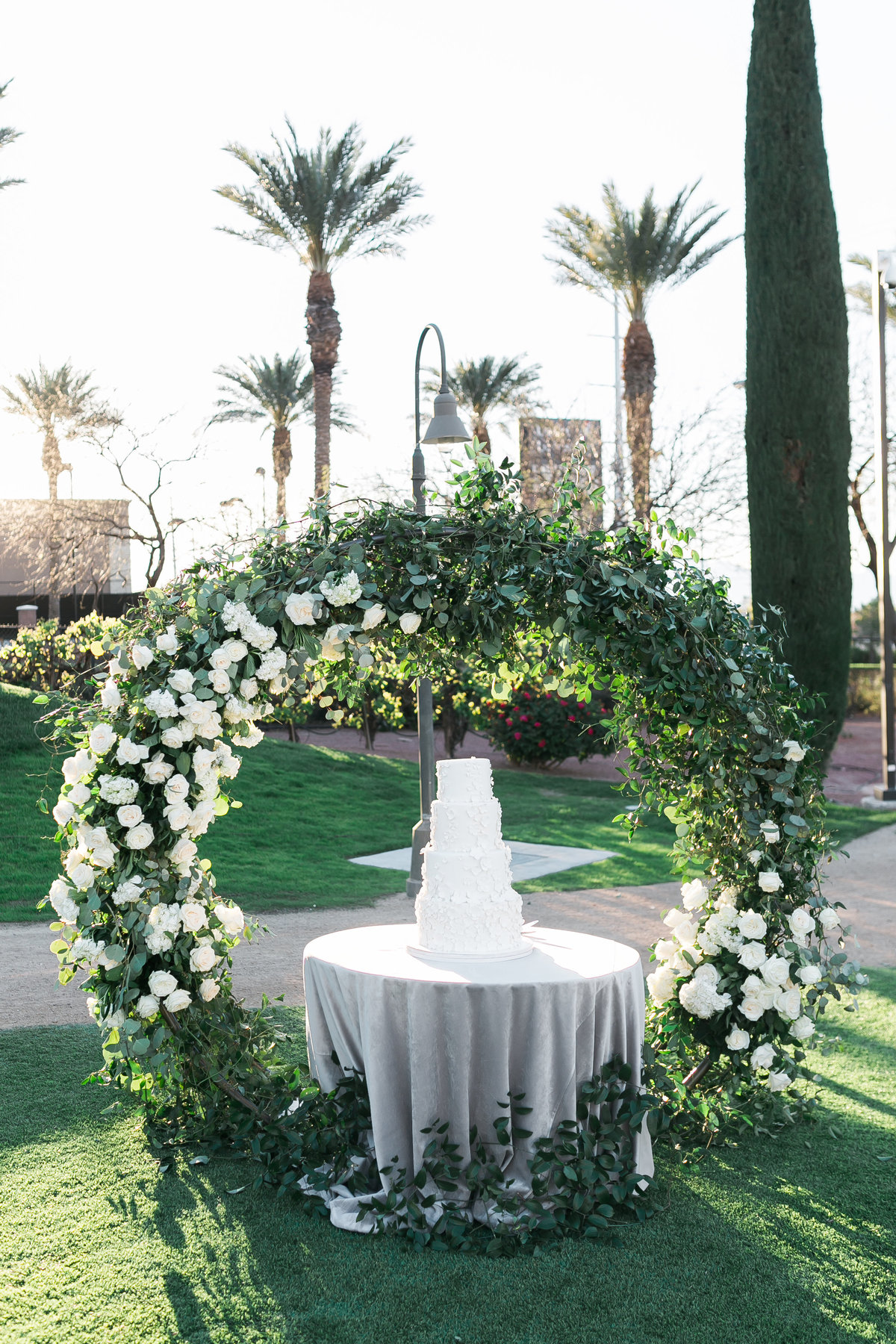 a photo of a wedding cake display with a white and greenery floral arch and grey velvet linen at a wedding at Green Valley Ranch in Las Vegas