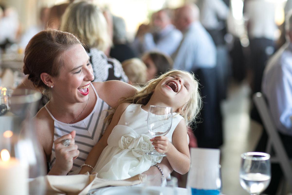 photo-journalistic candid wedding guests and flower girl laughing at wedding reception at The  Veranda at the Whitcomb, St. Joseph, Michigan, Lake Michigan Weddings, photographer Charlene Gurney