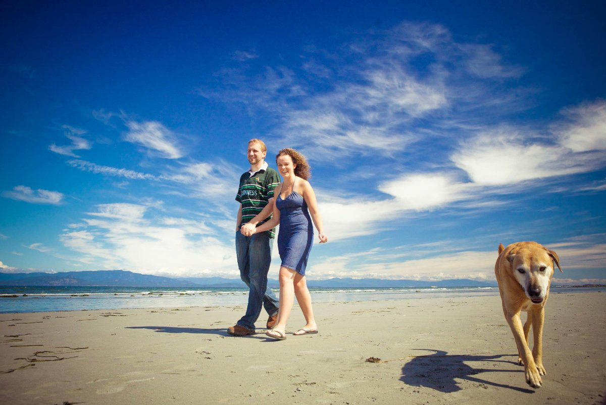couple holding hands on Parksville Beach with their dog