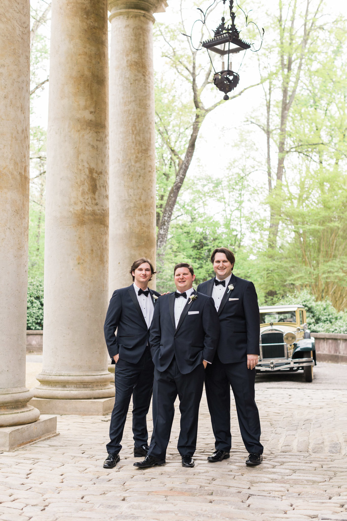 Three brothers have their portrait taken at the front steps of the Swan House. Photo by luxury destination wedding photographer Rebecca Cerasani.