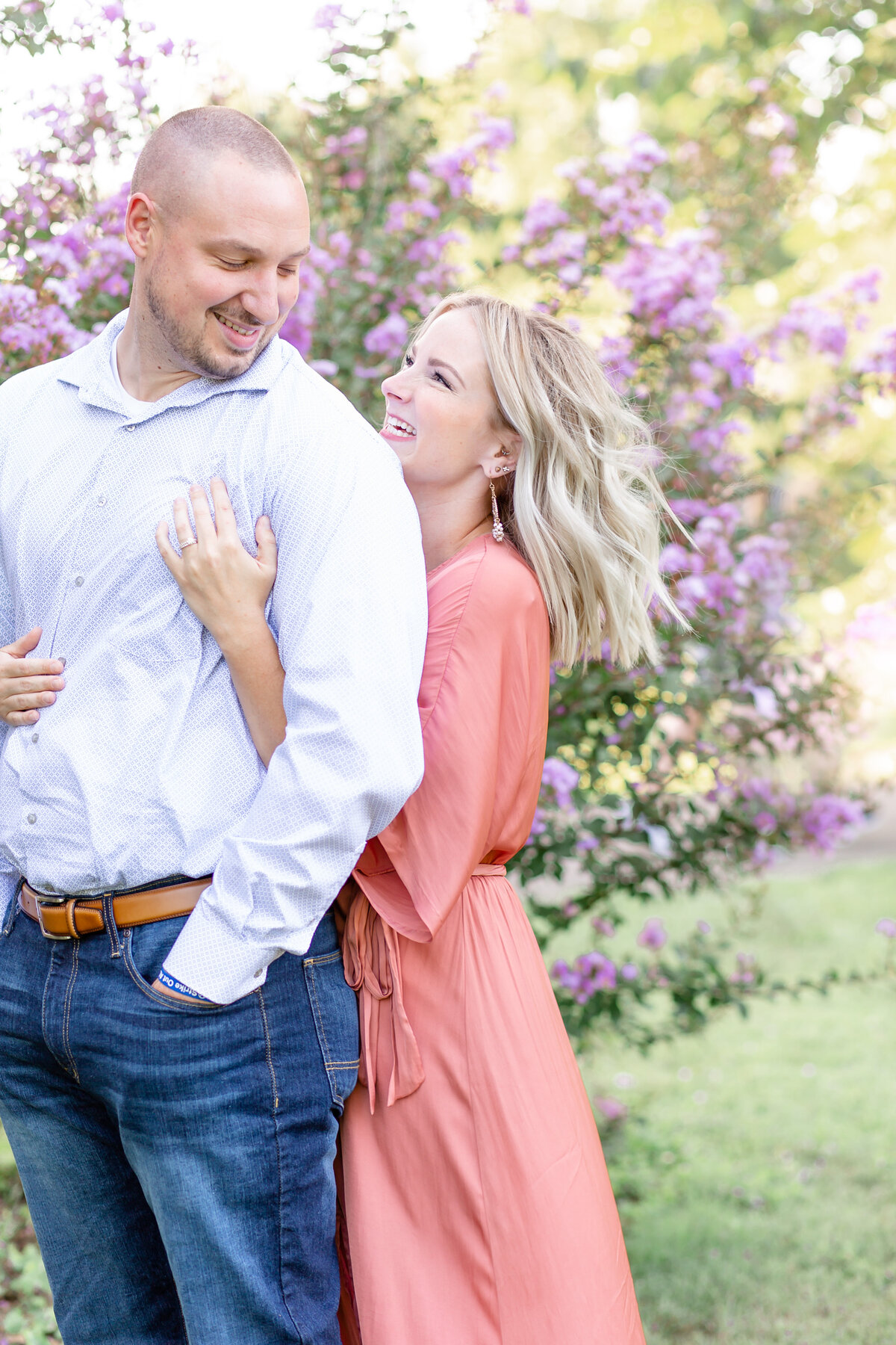 Summer Sunset Engagement Session with pink maxi dress couple laughing  by purple flowers  at Tower Grove Park in St. Louis by Amy Britton Photography Photographer in St. Louis