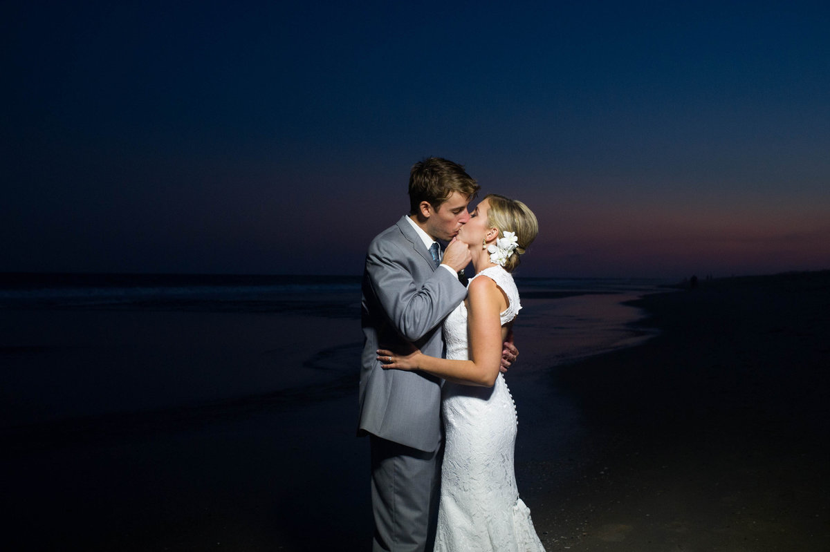 sunset on beach with bride and groom kissing