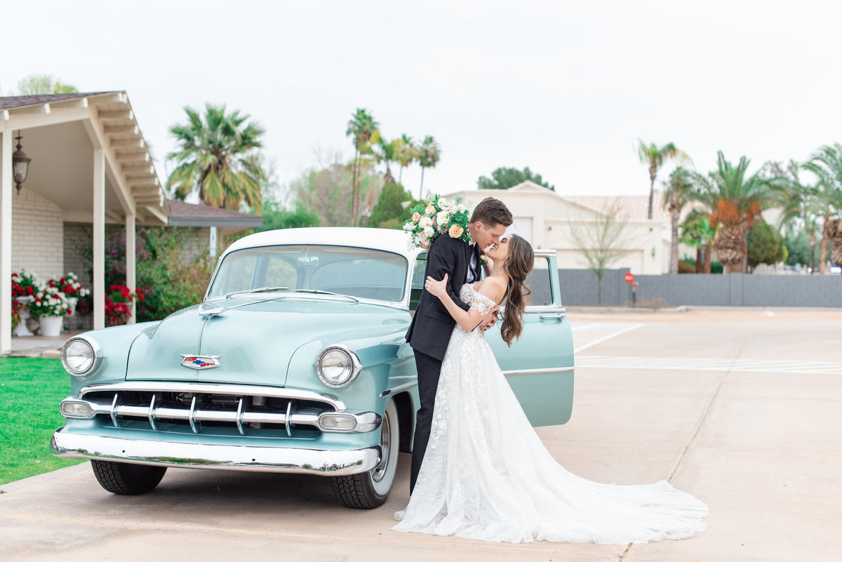 Bride and groom hold each other in front of a vintage car kissing