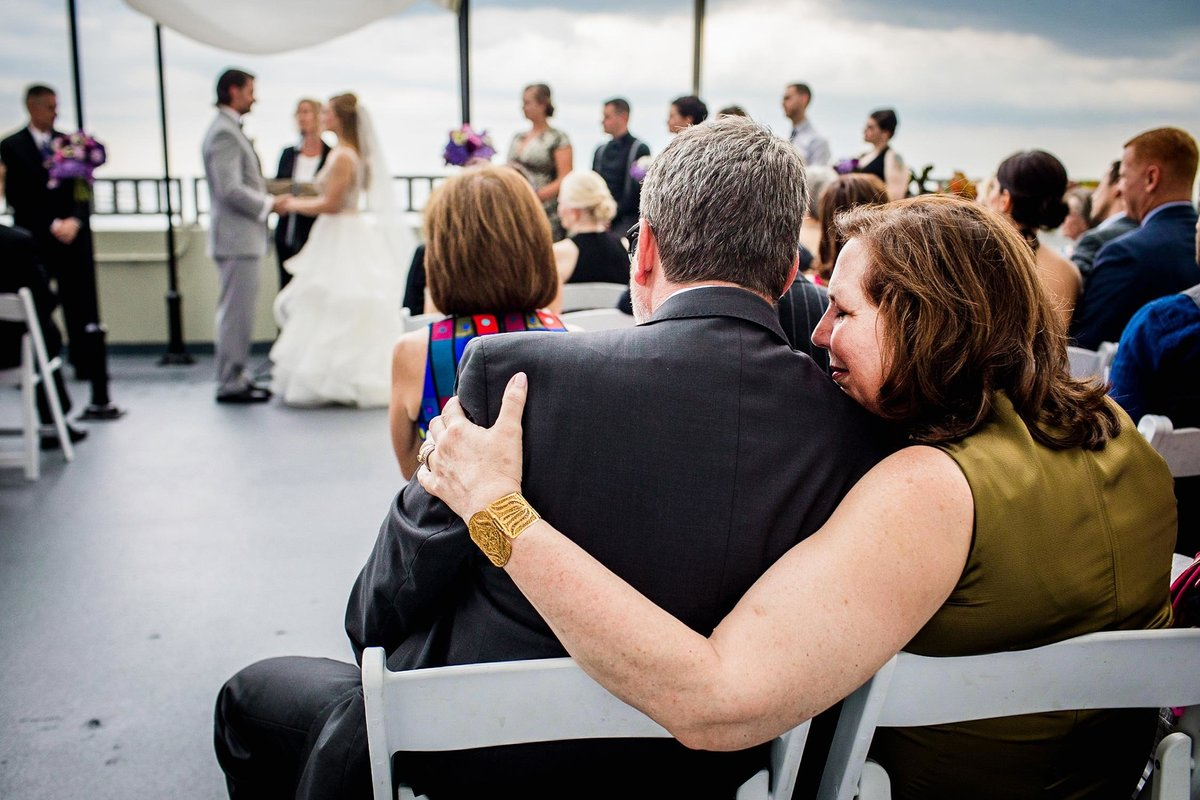 A couple embraces while watching a W Chicago Lakeshore wedding ceremony.