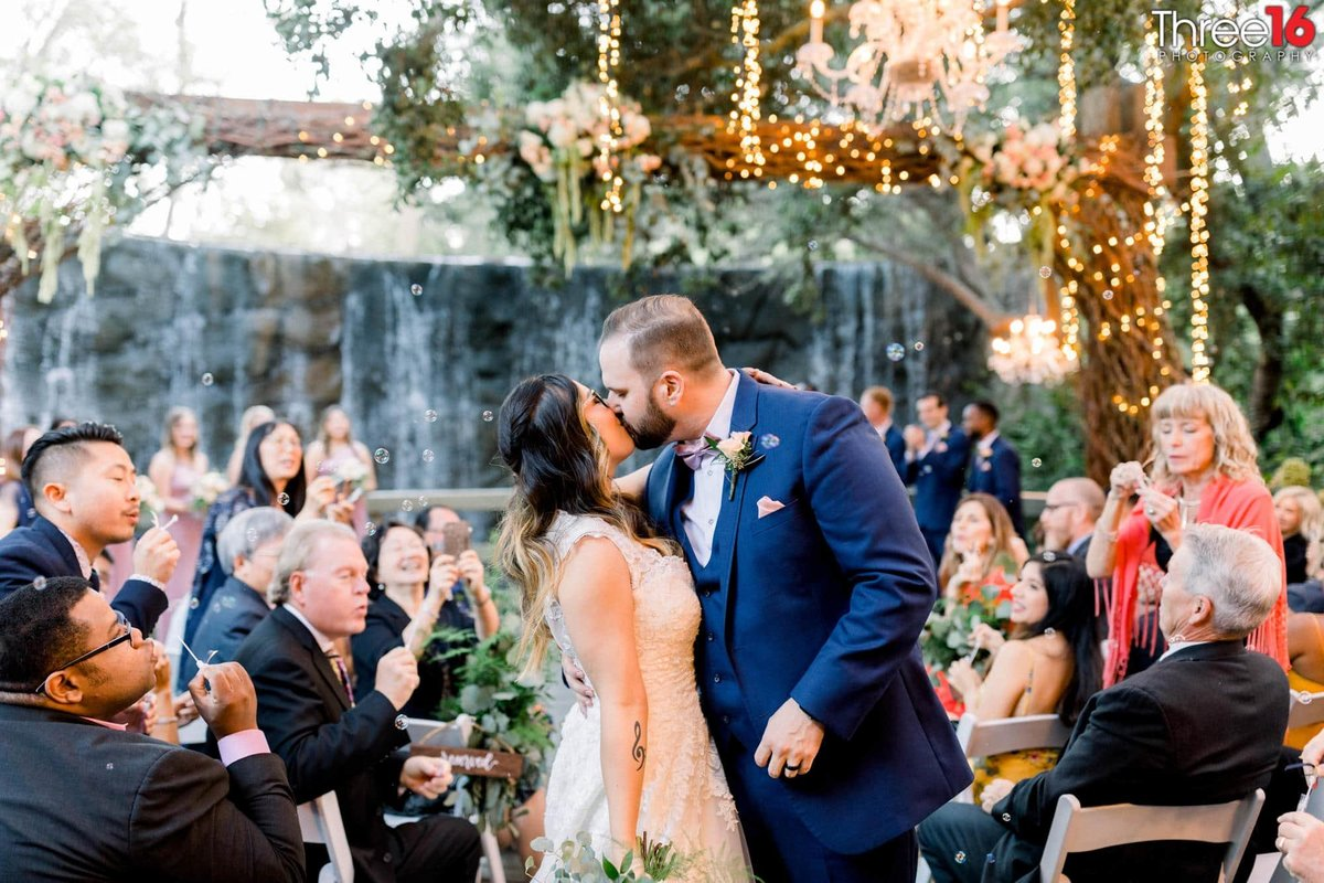 Groom kisses his Bride at the end of the aisle walkway