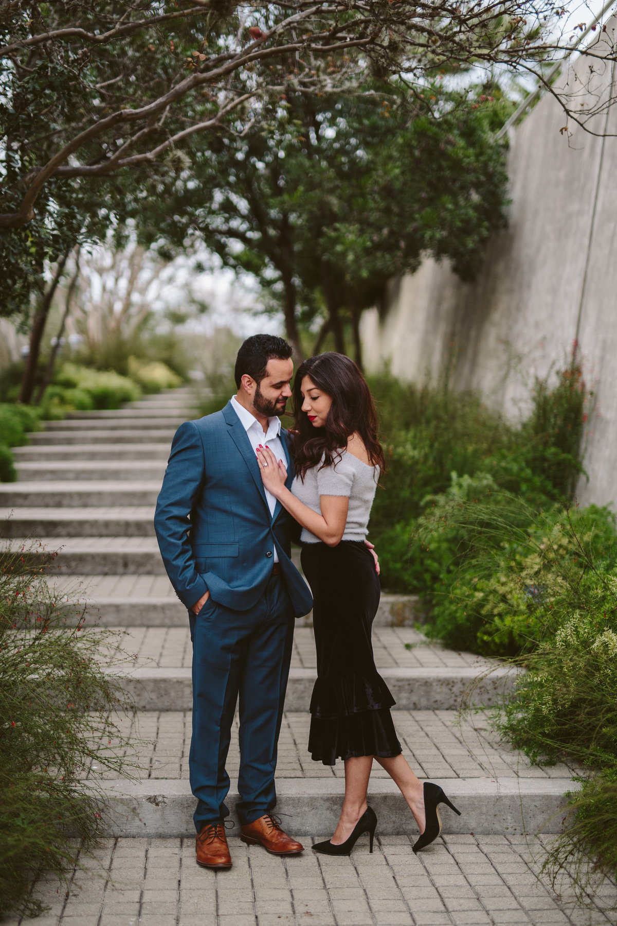 Woman with her hand on fiancé's chest over his heart and standing on steps at the San Antonio Botanical Garden.