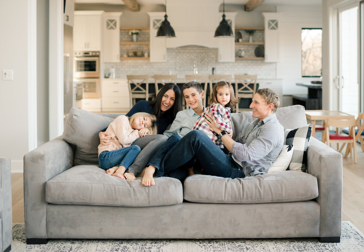in home lifestyle family photography of everyone cuddling on a couch