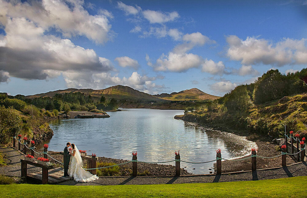 bride wearing a layered tulle, princess style wedding dress kissing her husband wearing a grey tailcoat, while standing on a wooden bridge overlooking Golden Cove at the Sneem Hotel in Kerry