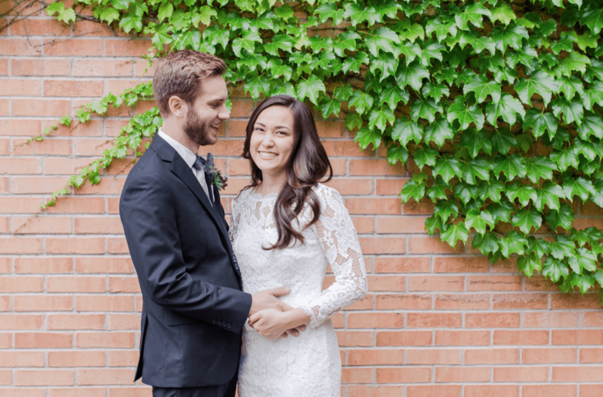 Bride and groom in front of a vine brick wall in Lake Villa shot by Maira Ochoa Photography