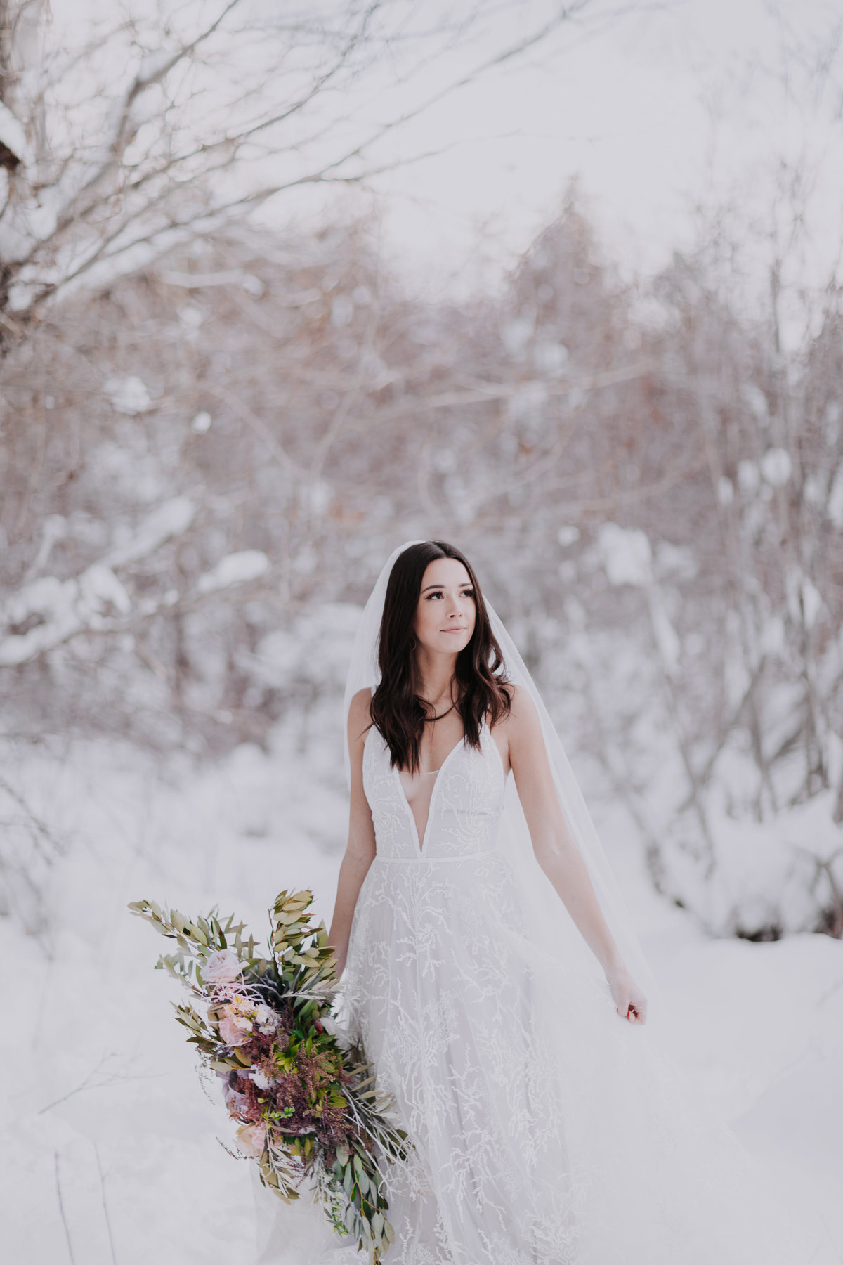 Crystal Peak Park Reno wedding pictures bride poses in snow with bouquet