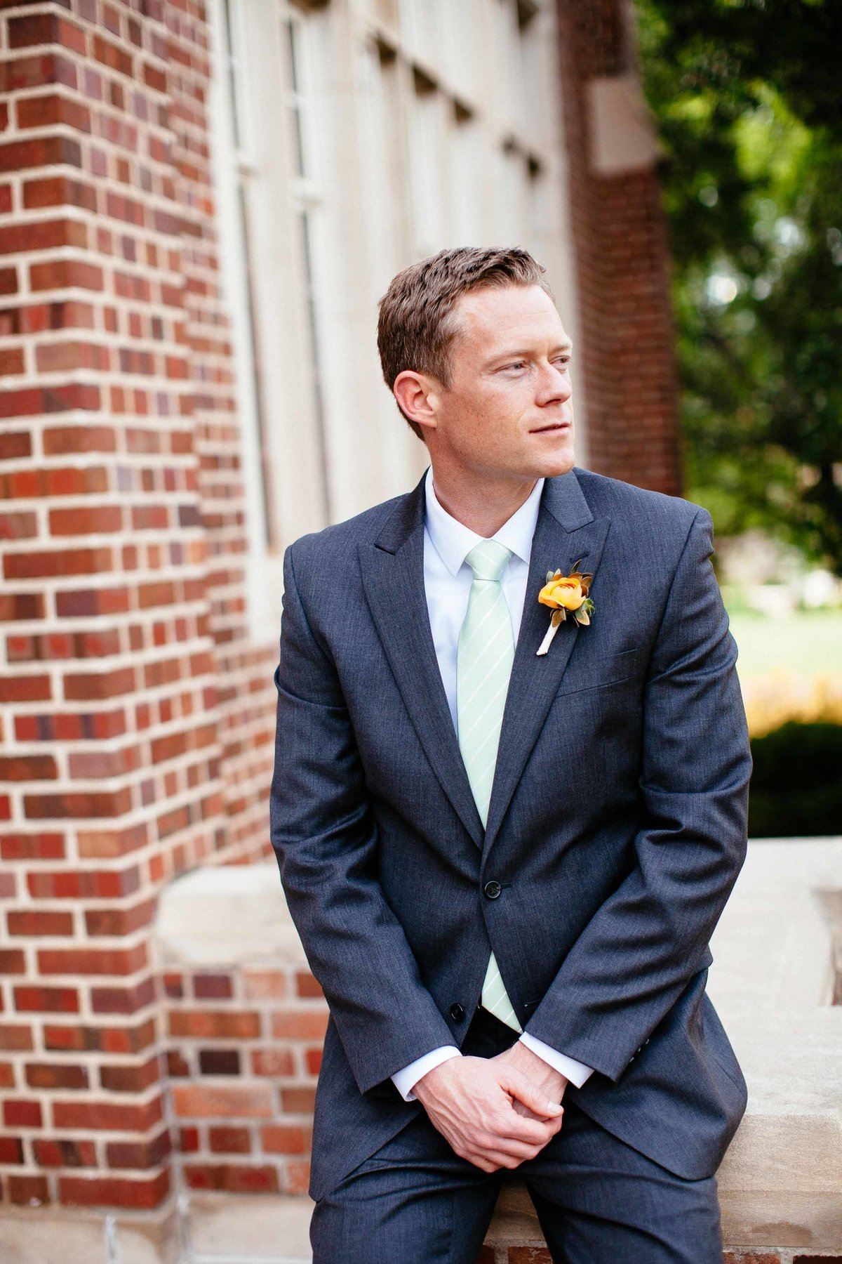 A groom in his suit sitting on a brick wall.