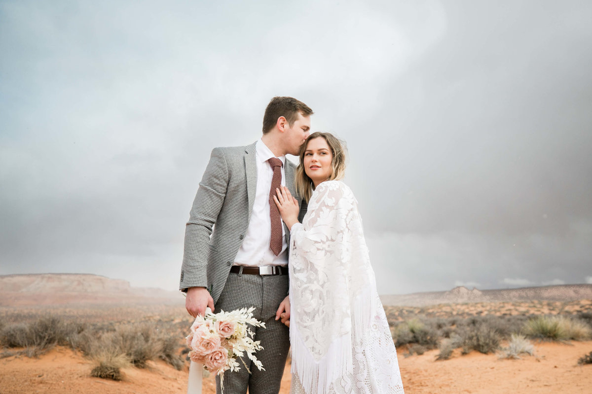 in the arizona desert the groom kisses brides head with a storm gathering behind the,