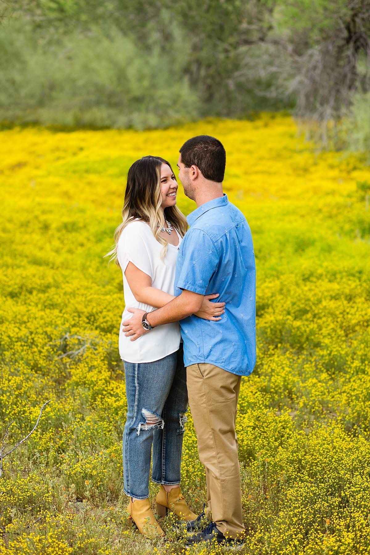 Couple smiling together in a yellow field of flowers during their Spring engagement session at Thunderbird Mountain by PMA Photography.