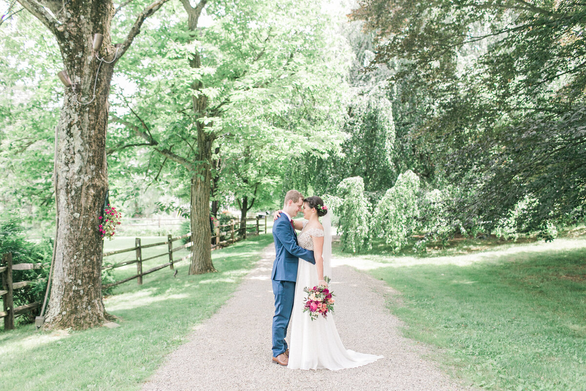Bride and groom embrace holding bouquet on tree lined path