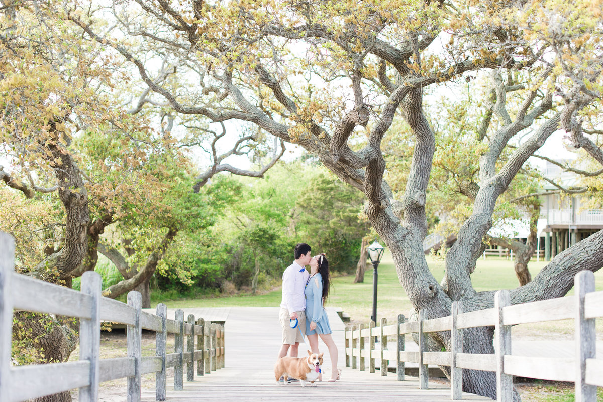 a bride wearing a short blue dress  kissing her fiance wearing khakis with a buttoned up shirt and a bowtie in front of a large tree with their corgi at Whalehead Club at Corolla Beach