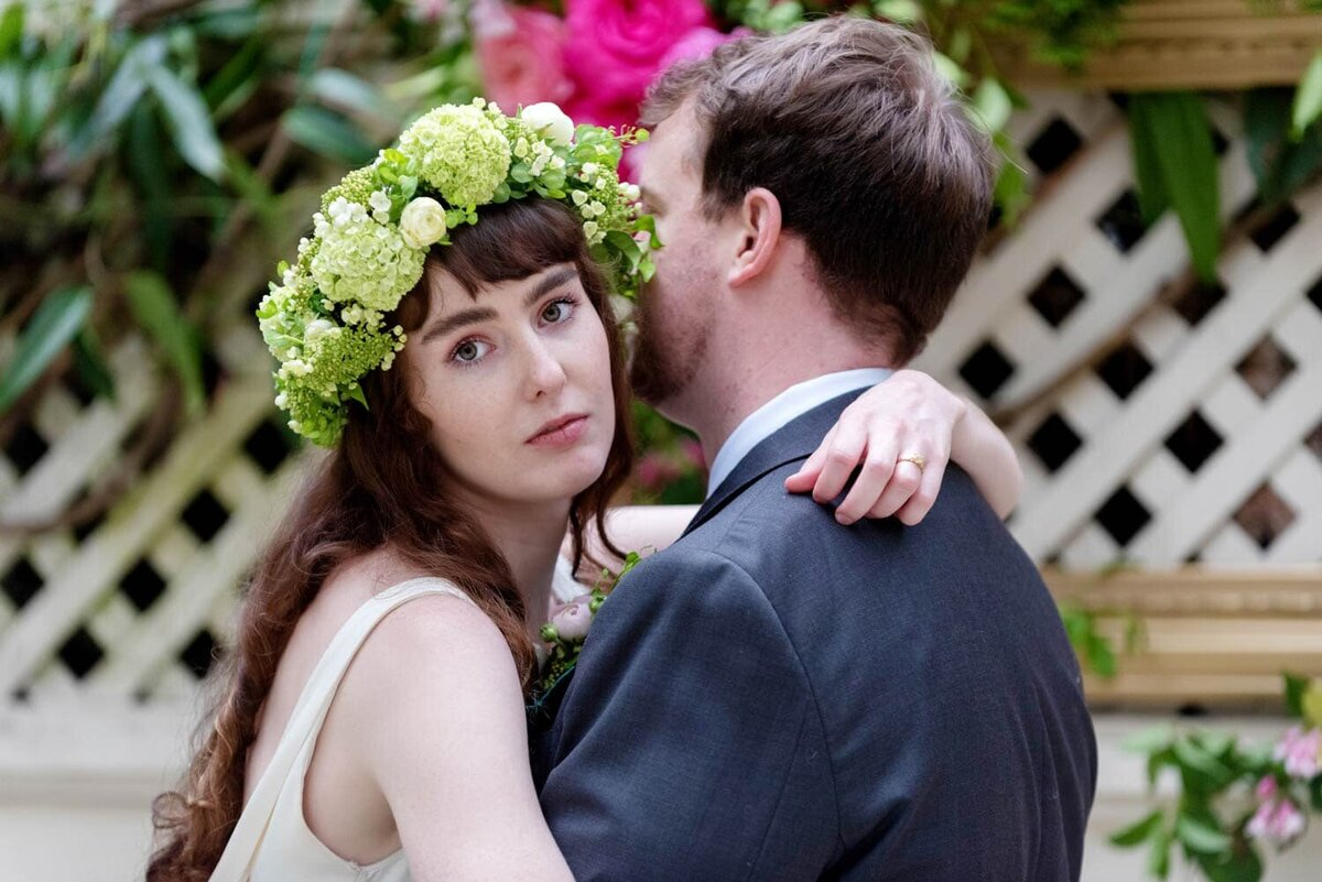 a pretty bride hugs a man while looking at the camera wearing a green flower crown