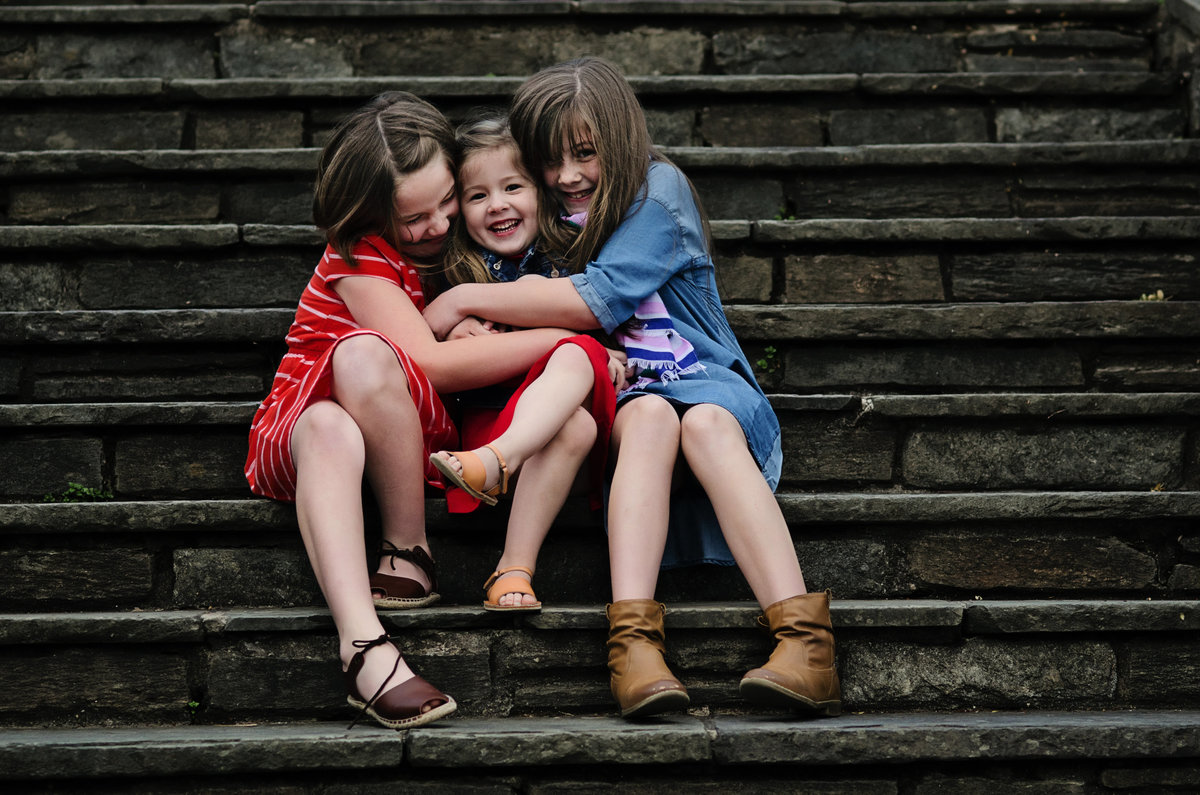 Portrait  of three laughing sisters on the steps at Glenview Mansion in Rockville, Maryland taken by Sarah Alice Photography