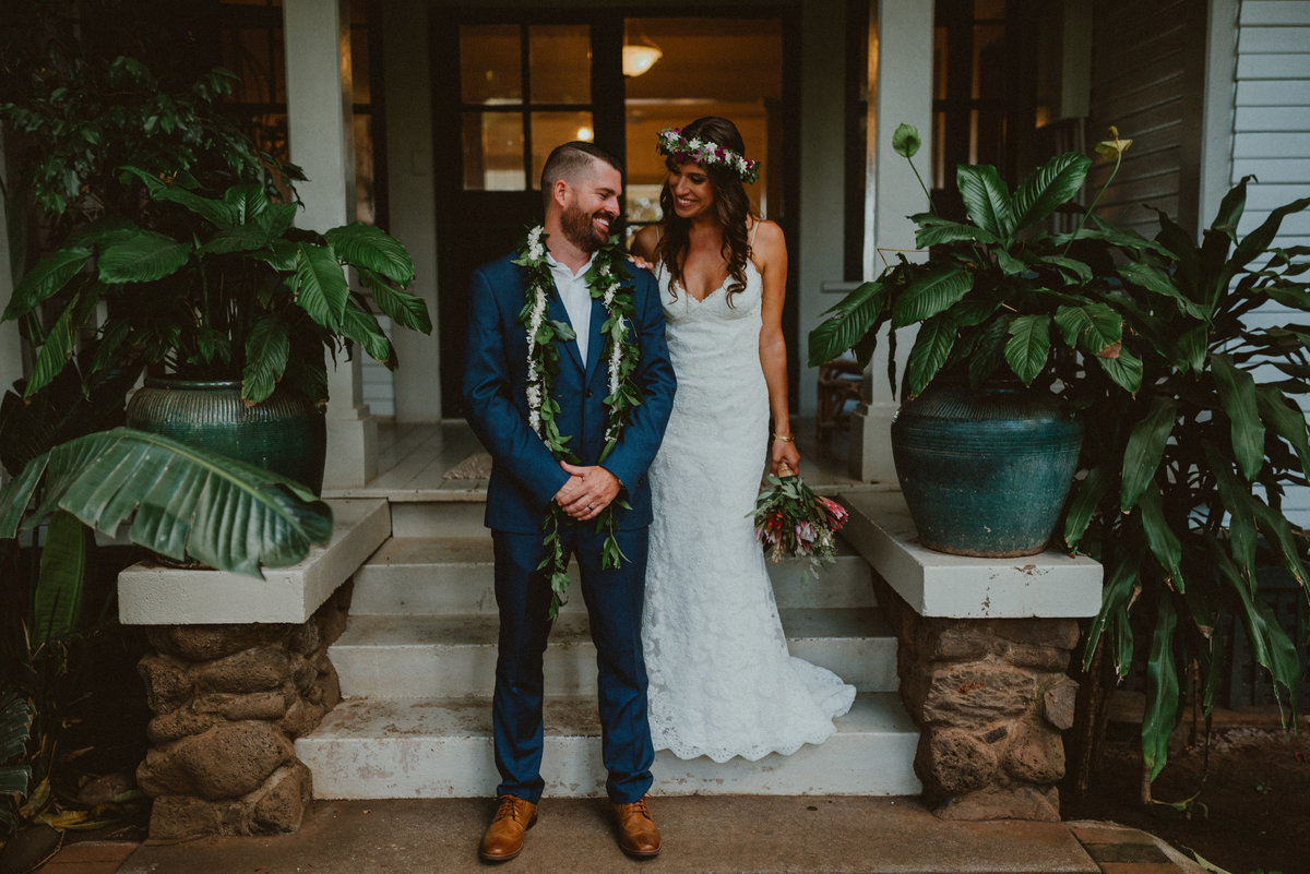 bride in white dress with flower crown and tropical bouqet  and groom in blue suit with flower and maile lei  smile at eachother  during first look surrounded by plants  on wedding day in Maui, Hawaii at Olowalu Plantation House